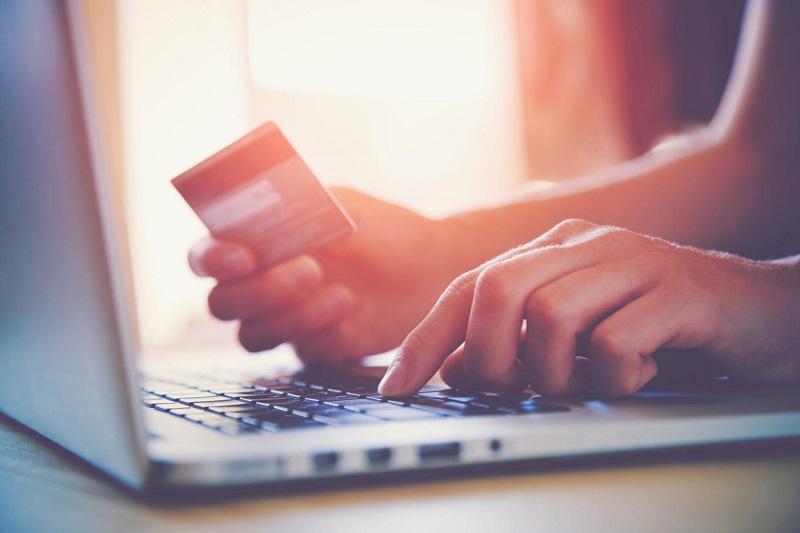 Pessoa com computador e cartão de crédito