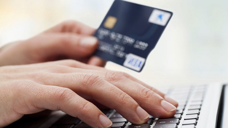 Pessoa com cartão de crédito e computador