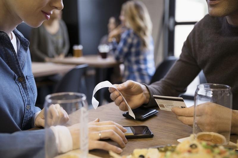 Pessoas pagando conta com celular