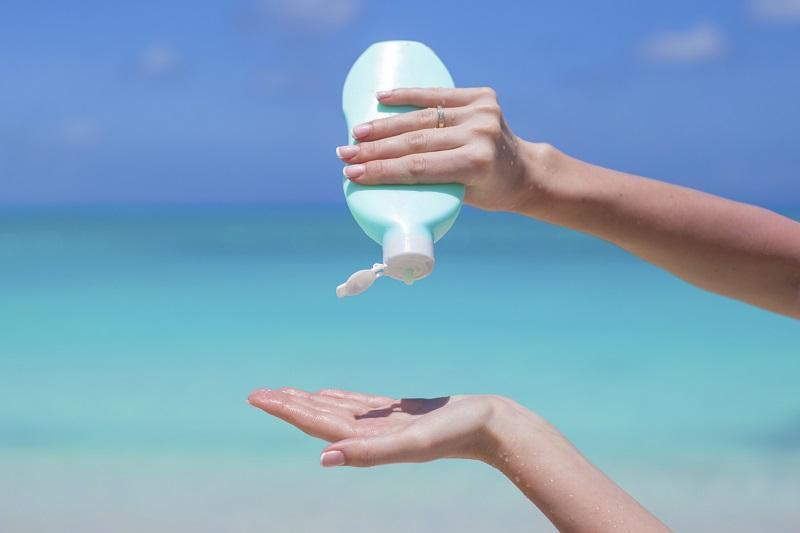 Pessoa passando protetor solar na praia