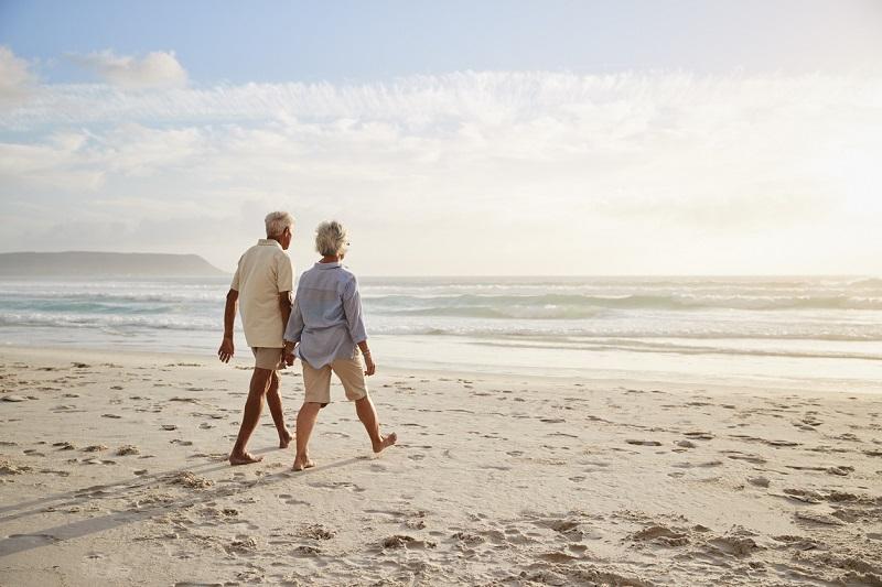 Idosos caminhando na praia